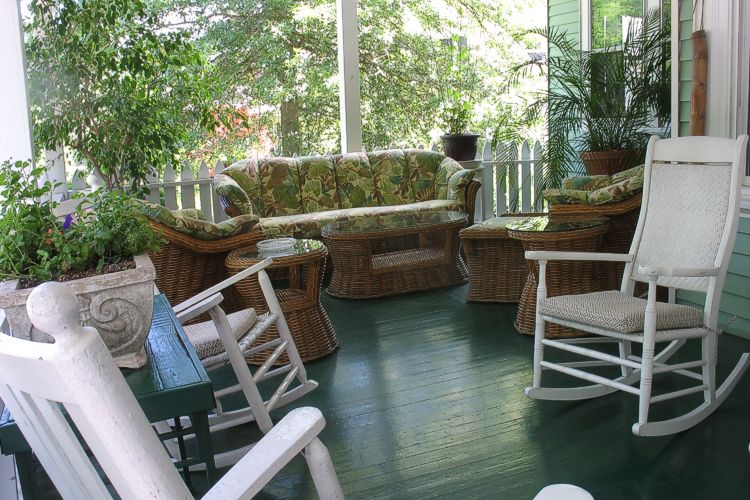 Couch, chairs, and tables on the front porch with windows looking into the inn in the background, and trees overhanging the porch.