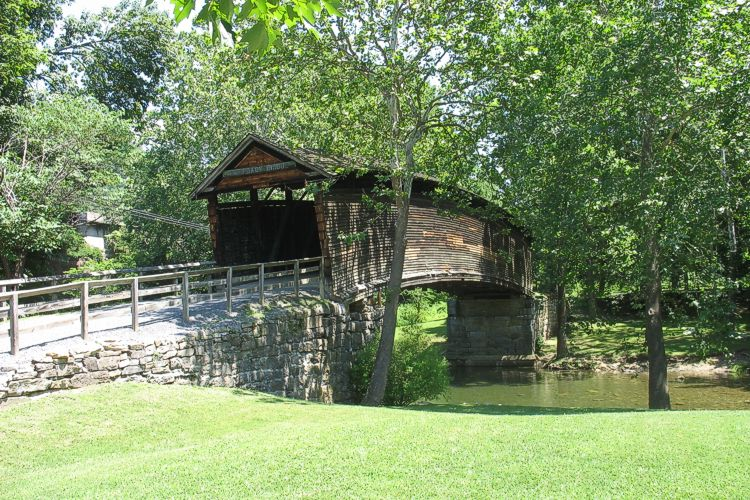 Humpback covered bridge with stone foundation over wooded riverbanks.