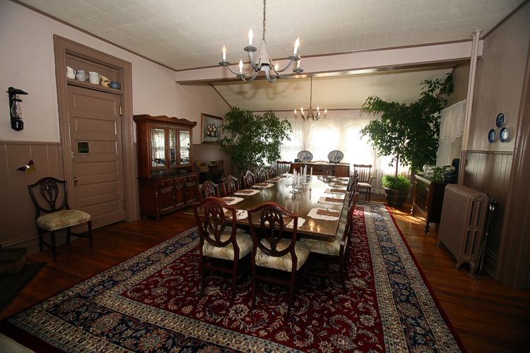 Dining room table with 14 place settings, ornate throw rug underneath with china cabinet and windows in the background.