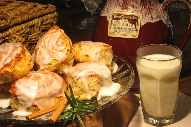 Plate with iced cinnamon rolls with glass of milk on right side.