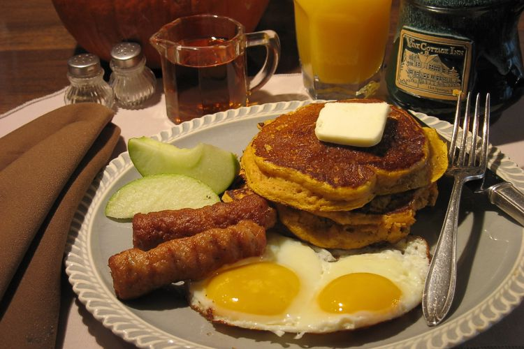 Two eggs, sunny side up, two slices of apple, four pancakes with butter, and two sausage links, pancake syrup and glass of orange juice.