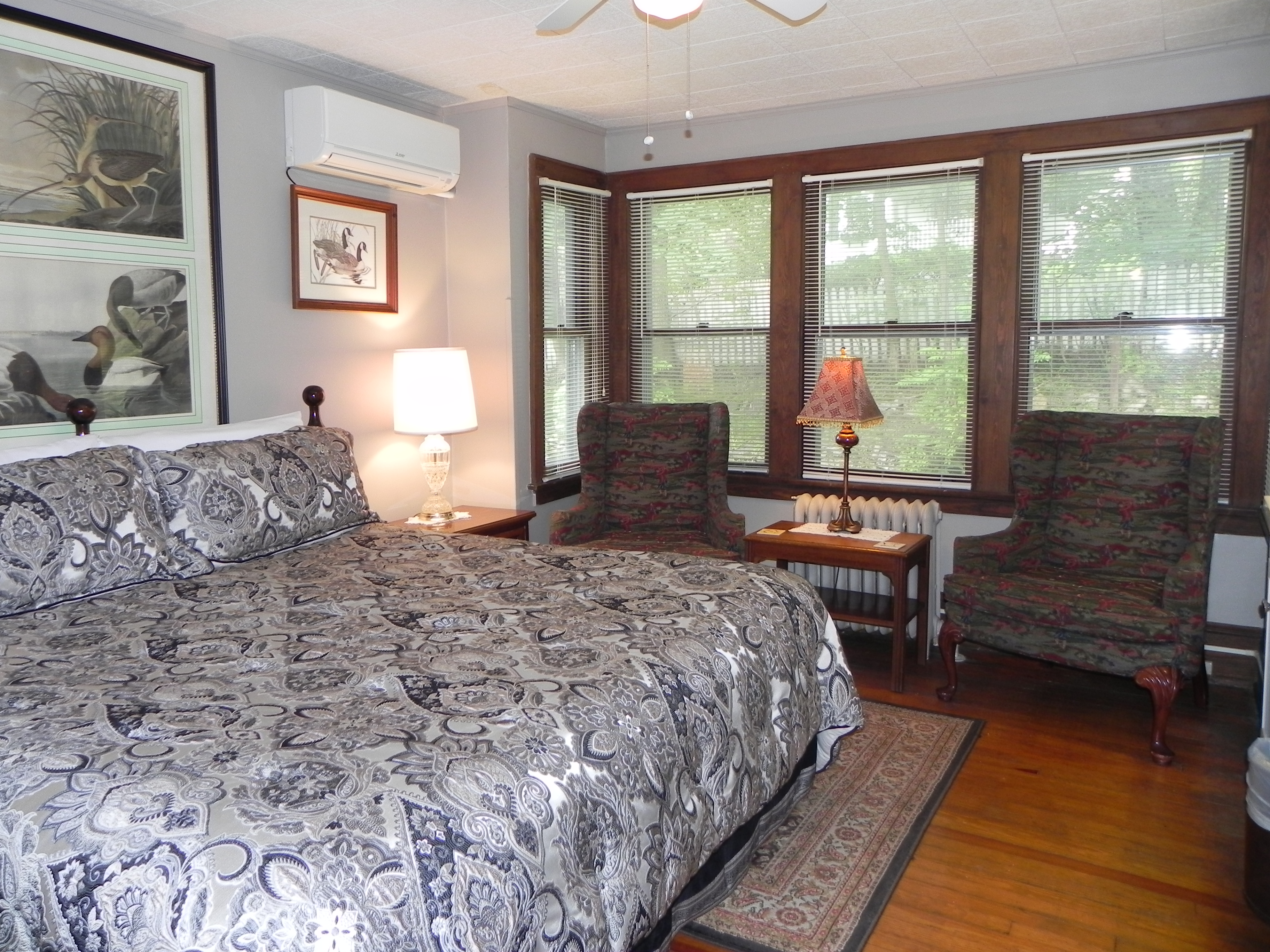 King size bed with silver and black comforter, hardwood floor, two armchairs and 5 windows overlooking back yard.