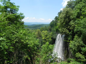 View of 80 foot Waterfall called Falling Springs surrounded by green trees with several mountain ridges in the background.