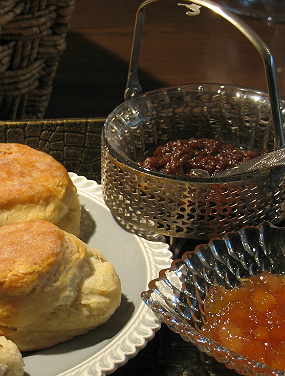 Flaky golden biscuts on a white plate served with two different fruit spreads.