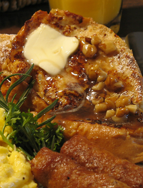 Golden brown french toast with butter, syrup, and finely chopped nuts accompanied by eggs and sausage.