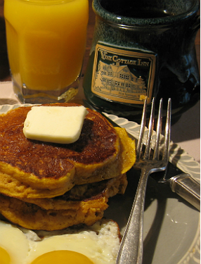Pumpkin pancakes topped with butter with orange juice on the side and coffee in a green mug.