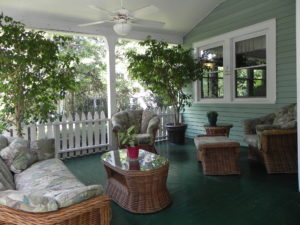 front porch of Vine Cottage Inn with two ficus trees and brown wicker outdoor furniture.