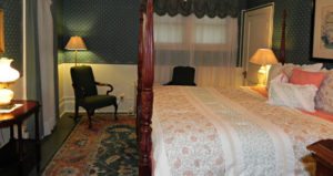 Four poster king size bed. Room decorated in blue and coral colors. Two arm chairs
