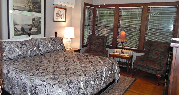 Room has king size bed with black and silver comforter. Room is decorated with pictures of ducks and has 5 large windows overlooking the back yard. Two green armchairs with side table between them complete the room.