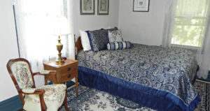 Soothing shades of blue decorate this room with a queen size bed.