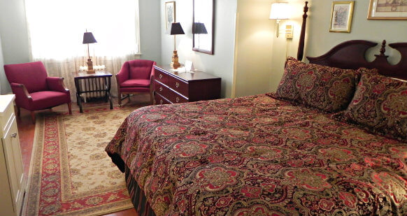 King size bed with burgundy and gold comforter. Room has large gold and burgundy area rug over hardwood floor. Room also contains a dresser and two burgundy armchairs with a side table in between.