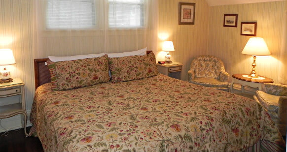 King size bed in a corner room with a cream colored floral comforter. Room has one night stand on either side of bed. Two armchairs with a side table provide a sitting area.