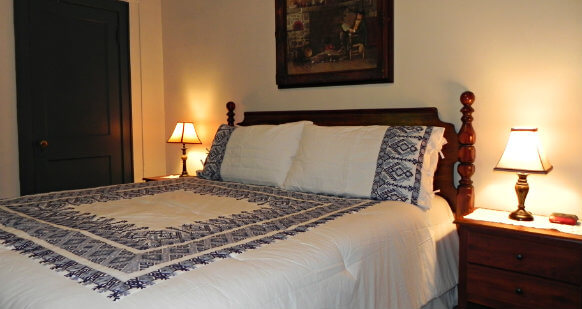 King size bed covered with a white comforter with square geometric pattern in a navy blue. There is a night stand on either side of the bed.