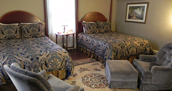 This room has two queen beds with a nightstand in between them. Comforters are Navy and gold. A large cream, gold and dark blue area rug covers the hardwood floor. Two grey arm chairs with one ottoman complete the room.