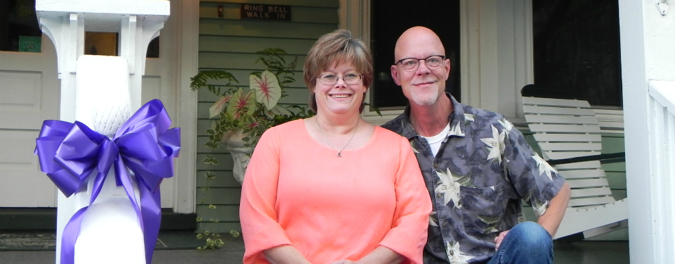 Picture of owners Tammy and Dave sitting on front steps of inn