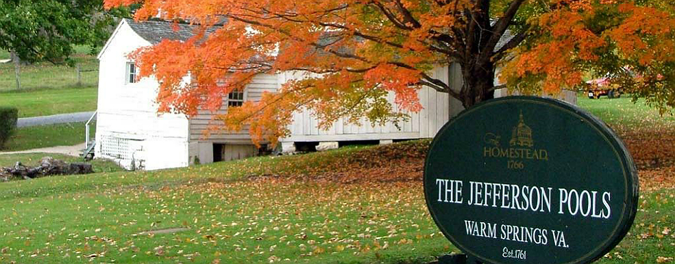 White house surrounded by green and orange fall foliage with a green sign for The Jefferson Pools in front.