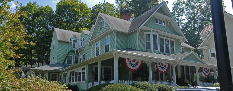 Front of the inn with bushes in front, colorful flags draped over the porch, and trees in the background.