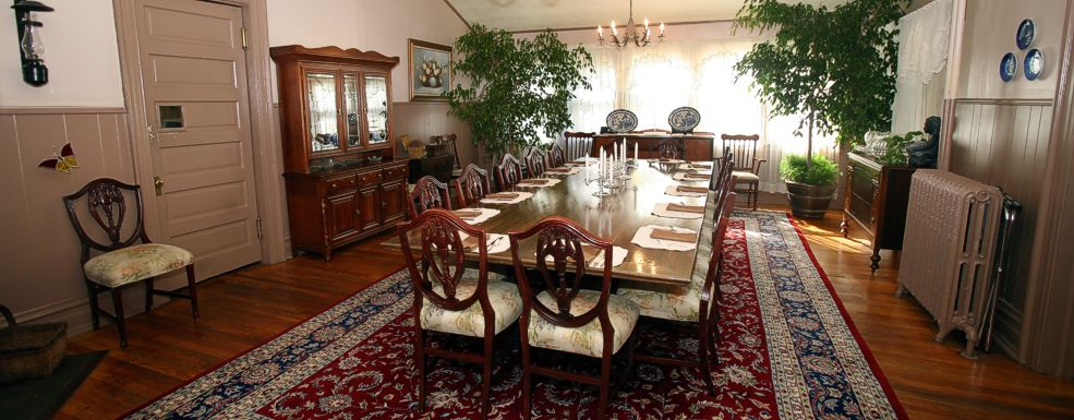Dining room with long table that has 14 place settings with an ornate carpet and bright green plants in the corners.