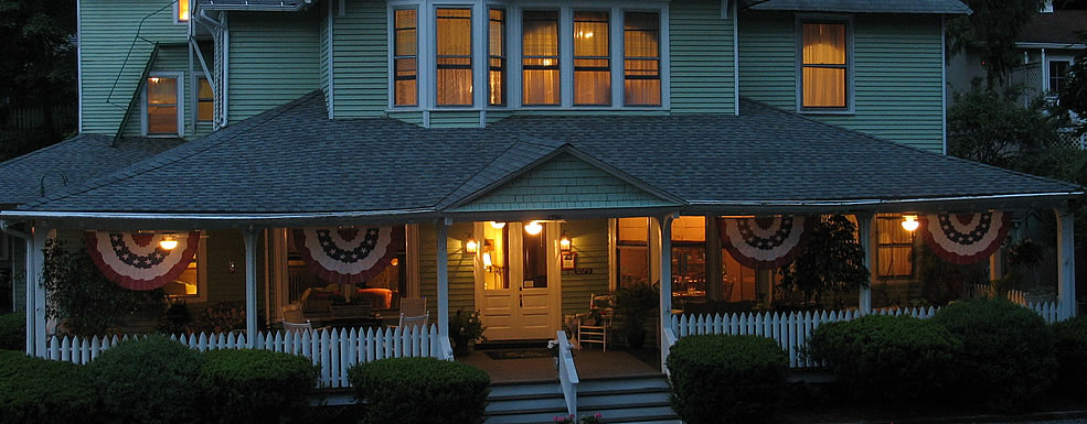 Front of the inn at night with red white and blue flags hanging from the porch and inviting lights in every window.