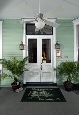 Front door of inn with plants on either side and a welcome mat in front.