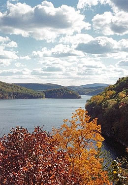 View of Lake Moomaw with trees showing red and orange fall foliage in foreground and beautiful green lake banks stretching off into the distance.