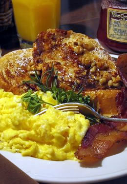 French toast with scrambled eggs and bacon, cup of orange juice in the background.