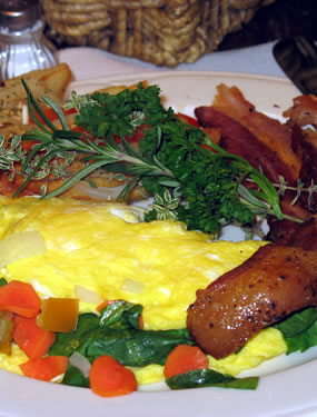 Veggie omelet with two strips of bacon and a parsley garnish.
