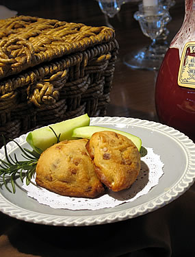 Two scones on a plate with two slices of apple and a decorative garnish.