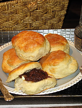 Plate of biscuits with one broken in half and loaded with a dark red jam.