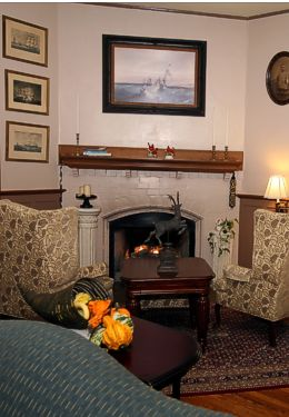 Burning fireplace with table and two chairs in front, with a painting hanging over the mantle.