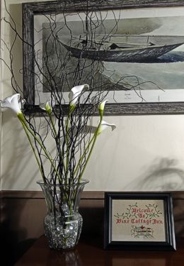 Table with vase holding lilies next to a framed needlepoint, underneath a painting of a boat on the shore.