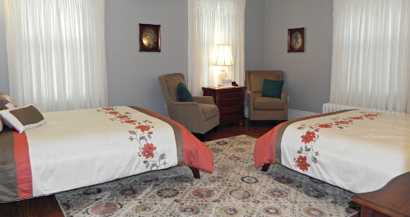 Two Queen beds with cream, brown and orange floral comforters. Room has large cream patterned area rug between the two beds. Two brown arm chairs with a side table between them are located in the corner in front of one of the three windows.