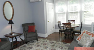 Separate sitting room with two chairs, pull out sofa and table with 4 chairs