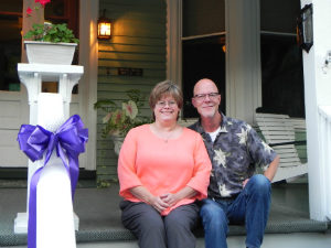 Owners Tammy and Dave sitting on the front porch of Vine Cottage Inn